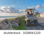 couple driving a golf cart at... | Shutterstock . vector #1028061220