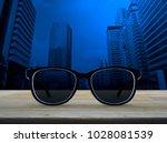 black eye glasses on wooden... | Shutterstock . vector #1028081539