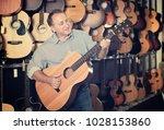 musician male is choosing... | Shutterstock . vector #1028153860