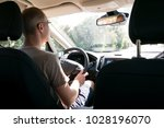 rear view  young man driving...   Shutterstock . vector #1028196070