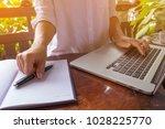 hand held pen on notebook and... | Shutterstock . vector #1028225770