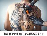 a tattoo artist makes a tattoo... | Shutterstock . vector #1028327674
