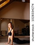 Small photo of Portrait of young woman practicing yoga indoor. Beautiful girl practice cobra asana in class