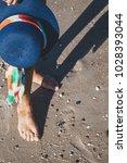 female feet in waves of the sea ... | Shutterstock . vector #1028393044