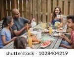 family enjoying breakfast... | Shutterstock . vector #1028404219