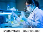 young female scientist using... | Shutterstock . vector #1028408500