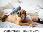 yong woman and her dog in home | Shutterstock . vector #1028419393