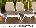 two beige plastic loungers in... | Shutterstock . vector #1028437564
