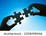 hands connecting two puzzle...   Shutterstock . vector #1028498446