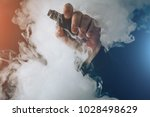 man hand shows vape device at... | Shutterstock . vector #1028498629
