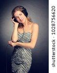 young cheerful girl listening... | Shutterstock . vector #1028756620