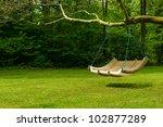 swing bench in lush garden.... | Shutterstock . vector #102877289