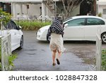 female under rain drops cover... | Shutterstock . vector #1028847328