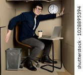 Small photo of Overcrowding concept. Full length portrait of angry young employee is sitting in confined carton office and expressing irritation from little space. He is pressing on walls