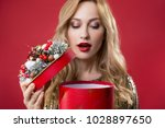Small photo of I cannot wait anymore. Portrait of serene female person opening box with present. Focus on case. Isolated on red background