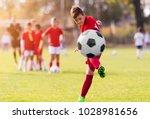 boy kicking football on the... | Shutterstock . vector #1028981656