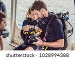 diver prepares his equipment... | Shutterstock . vector #1028994388