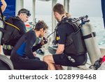 diving instructor helps a... | Shutterstock . vector #1028998468