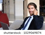 young businessman sitting... | Shutterstock . vector #1029069874