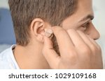 young man putting hearing aid... | Shutterstock . vector #1029109168