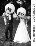 Small photo of Bride and groom walk with balloons with lettering 'Mr' and 'Mrs' across the lawn in park