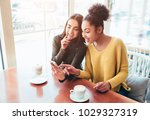 Small photo of Two cheerful and beautiful girls are sitting together near the table and watching something on the phone. They look relaxed and happy. Also girls are enjoying the time spending together