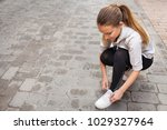 teenager girl crouching tying... | Shutterstock . vector #1029327964