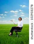 smiley businesswoman holding something on her hand at the meadow - stock photo