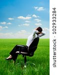 young woman relaxing in armchair at the meadow - stock photo