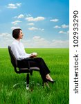 young businesswoman relaxing at the meadow with cup of coffee - stock photo
