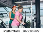 trainer helping to overweight... | Shutterstock . vector #1029408829