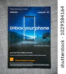 Small photo of PARIS, FRANCE - APR 26, 2017: Unbox Your phone advertising campaign for Samsung Galaxy Smartphone S8 from Orange Telecom on the last page of a fashion magazine newspaper