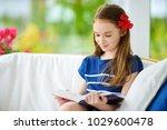 adorable little girl reading a... | Shutterstock . vector #1029600478