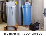 Small photo of New water softening unit or tank ready alongside the old one for installation to replace it in a utility room with a portable tool kit in a box on the floor