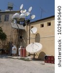 Small photo of near Polis, Cyprus - August 03 2004: collection of white satellite dishes upon and next to a usual house