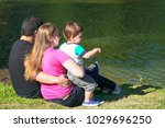 family sitting by the lake | Shutterstock . vector #1029696250
