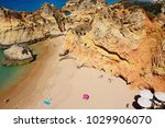 Small photo of PRAIA DA ROCHA, PORTUGAL - JUNE 7, 2017 - Elevated view of tourists relaxing on the beach with large rocks to the rear, Praia da Rocha, Algarve, Portugal, Europe.