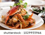 Chilli Blue Swimmer Crab cooked meal on a white plate in a restaurant setting with other dishes in the background
