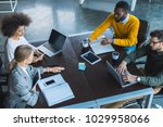 Small photo of high angle view of multicultural businesspeople working with digital devices in office