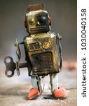 Small photo of beaten up robot toy with a black eye