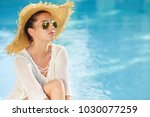 woman in hat relaxing beside... | Shutterstock . vector #1030077259
