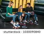 Small photo of family wearing roller skates before skating in skate park