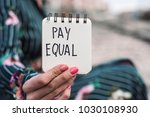Small photo of closeup of a young caucasian woman outdoors showing a notepad with the text pay equal written in it