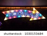 Small photo of Illuminated wall mounted arrow sign with the word Thrils written on it