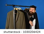designer hides among suits on... | Shutterstock . vector #1030206424