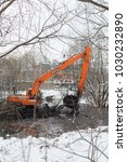Small photo of Balashikha, Moscow area, Russia - December 07, 2017: The excavator cleans the Malashka river bed from silt, dirt and thickets