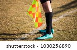 Small photo of Football soccer arbiter assistant stands at sideline observing the match with flag at hands. Blurred green field background, close up.