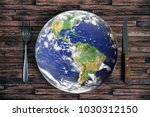 Small photo of The planet Earth plate with a fork and knife on a wooden background. World hunger concept. Feed the world.