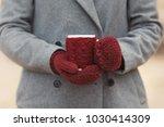 closeup hands in knitted gloves ... | Shutterstock . vector #1030414309
