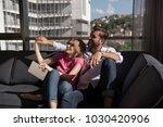 young couple sitting on sofa... | Shutterstock . vector #1030420906